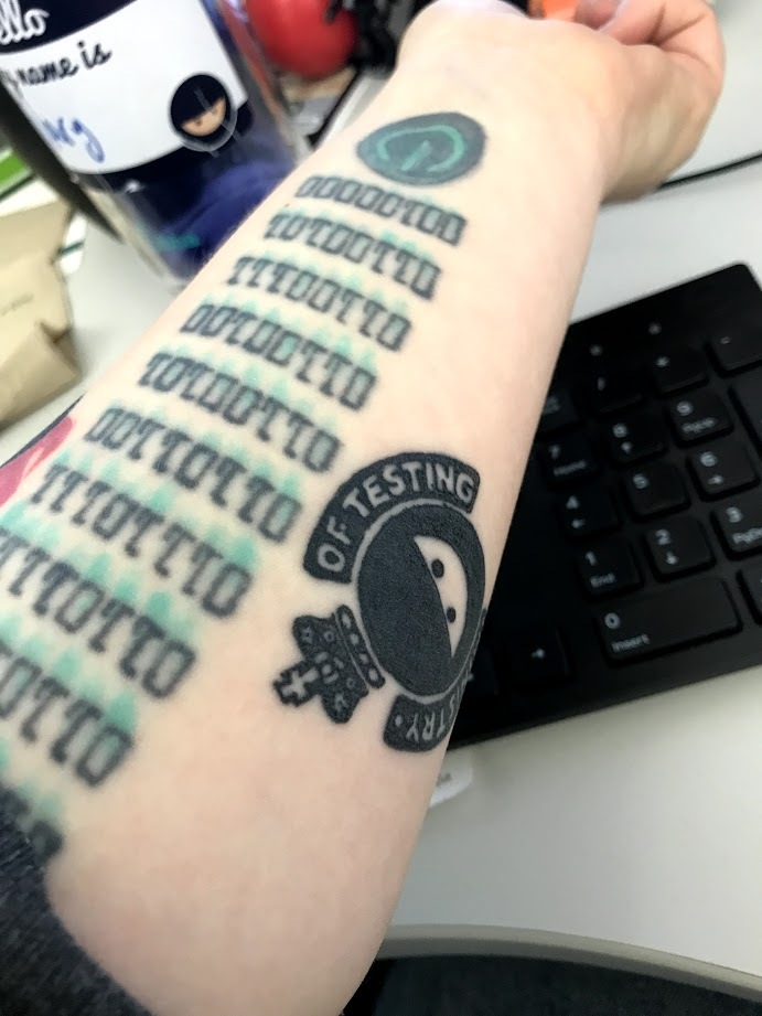 Photo of an arm with a Ministry of Testing logo tattoo