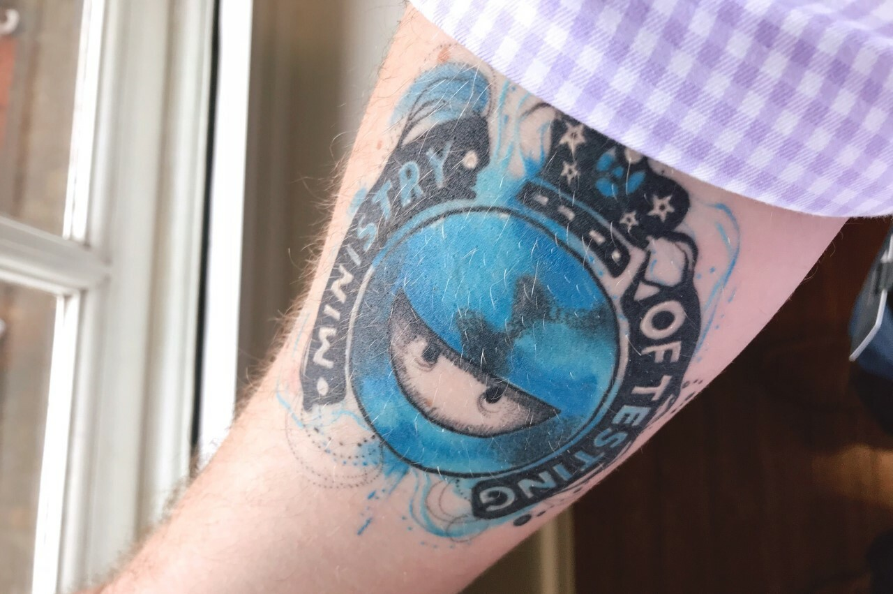 A photo of an arm with a Ministry of Testing logo tattoo